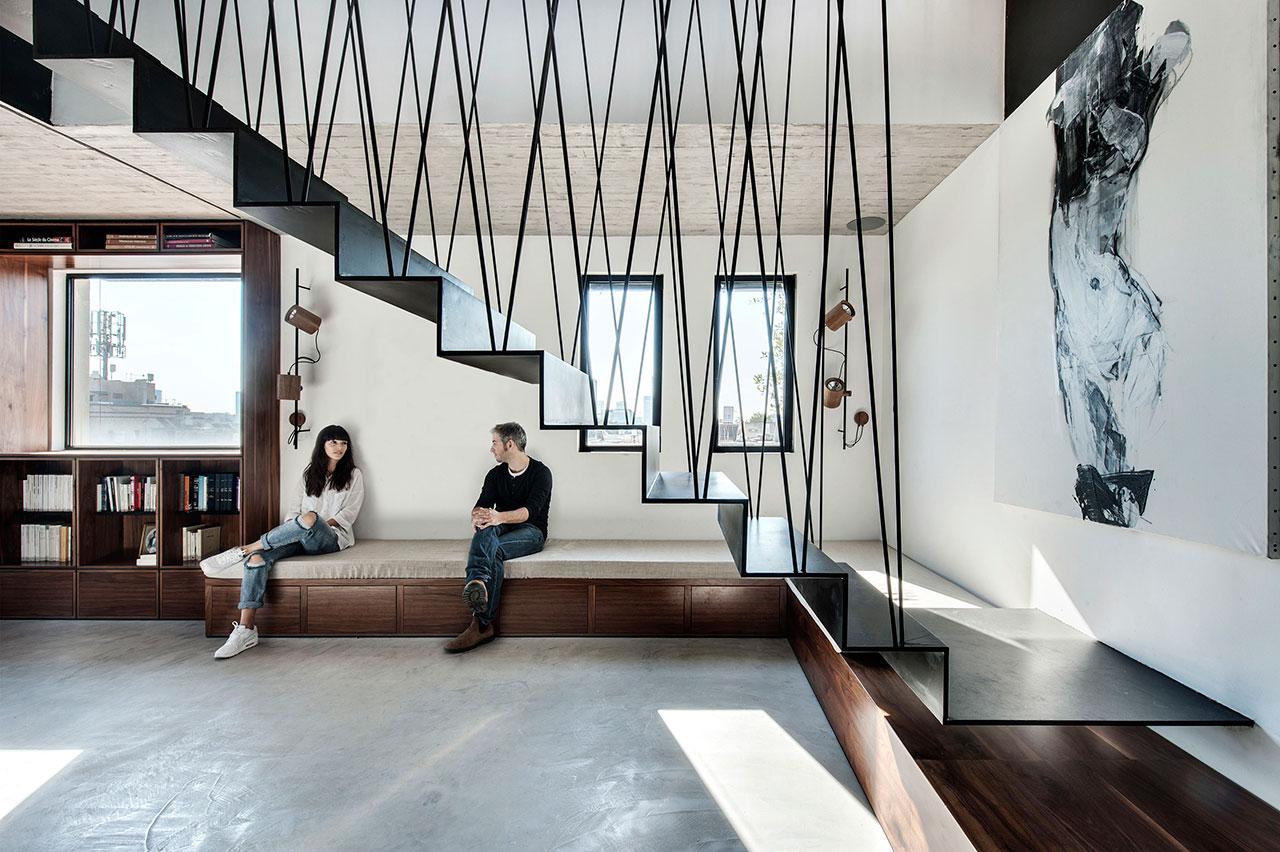"""这栋位于以色列特拉维夫的160平方米复式顶层公寓是由当地的建筑工作室Toledano + Architects设计的。设计团队面临的主要挑战是将安静的父母和儿童区域的隐私结合起来,这一挑战在空间的巧妙规划中得到了解决:在底层中,父母和孩子的区域被一个集中的模块和灵活的生活空间分隔开来。而在上层,大的厨房、休息室和环绕的屋顶平台相互融合,从而形成了一个无缝衔接的概念,即消除内部和外部空间的界限。 这个家庭想要一个""""别致而好玩""""的空间来满足所有人的需求;就像这样,孩子们的房间被设计用来"""